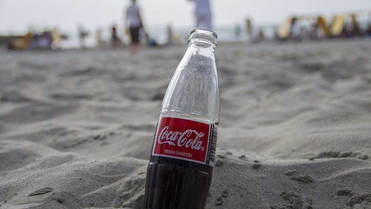 Una botella de Coca Cola en la arena de una playa