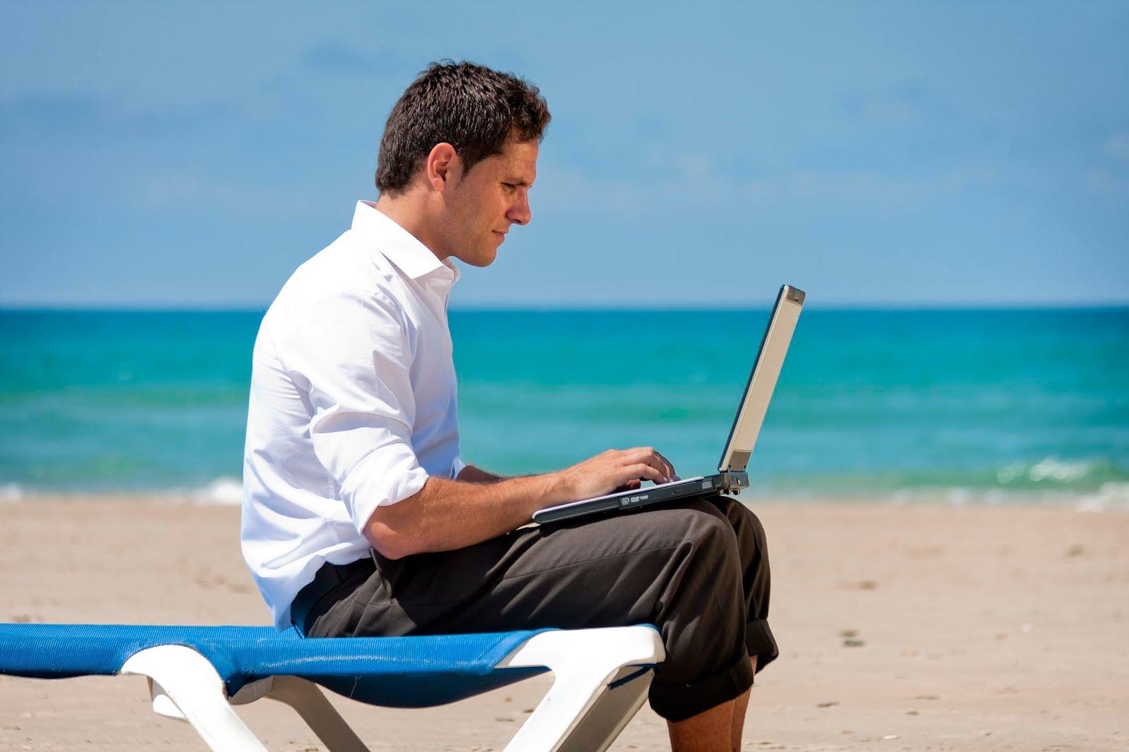Un hombre en una playa trabando con su ordenador