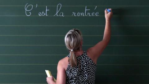 Una profesora escribiendo en la pizarra