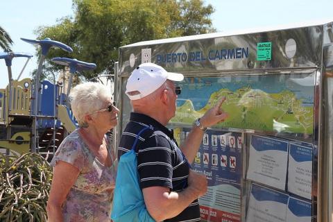 Dos turistas en un panel informativo del Puerto del Carmen, Lanzarote