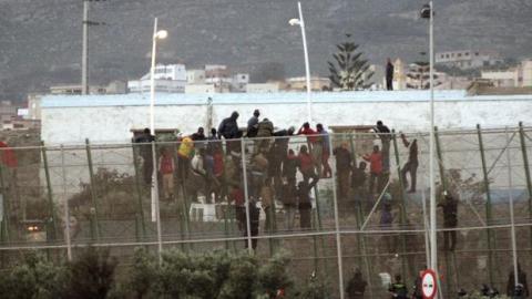 Inmigrantes saltando la valla de Melilla