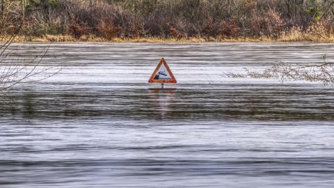 Señal de tráfico en medio de un río inundado