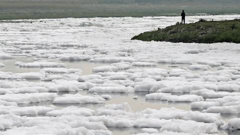 Espuma sobre el agua contaminada del río Yamuna