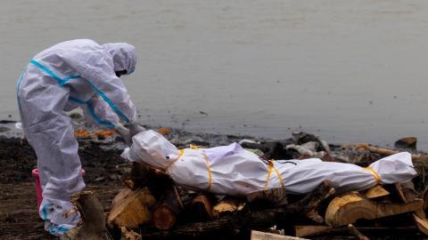 Un hombre junto al cadáver de un fallecido por covid-19 antes de su cremación a orillas del río Ganges, en Garhmukteshwar (Uttar Pradesh, la India), el 6 de mayo de 2021.